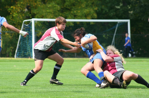 Andrea Portillo '14 is tackled by two WPI players. The rugby team's new coaches have been working with the players to improve their skills and tactics, including offensive moves like tackling.